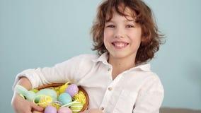 Lockigt rödhårigt barn i en vit skjorta med ett diagram av en påskkanin och en uppsättning av påskägg i en korg en pojke stock video