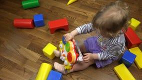 Lockigt tänd - den bruna flickan trycker på knapparna av en musikalisk leksak stock video