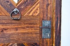 Locking mechanism and knocker. In burnished metal of an ancient wooden door Stock Image
