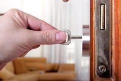 Locking or unlocking the door. Man is locking or unlocking a door Royalty Free Stock Images