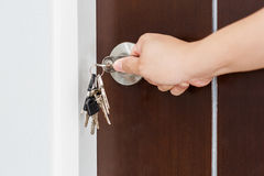 Locking or unlocking door with key by hand Royalty Free Stock Image