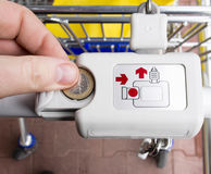 Locking and unlocking the supermarket trolley with one euro coin. Supermarket trolley - cart unlocking with one euro coin in Europe Union Royalty Free Stock Images