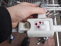 Locking and unlocking the supermarket trolley with one euro coin. Supermarket trolley - cart unlocking with one euro coin in Europe Union Stock Photo