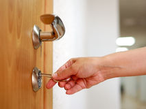 Locking up the door with a key Royalty Free Stock Photo