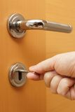 Locking up or unlocking door with key in hand Royalty Free Stock Images