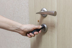 Locking up or unlocking door with key in hand. Locking up or unlocking door with key in hand Royalty Free Stock Photography