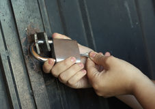 Locking up. Woman's hands locking up steel door with padlock Royalty Free Stock Images