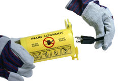 Lockout container. Gloved hands putting an electrical plug into a lockout tag container isolated with clipping path at original size Stock Photo