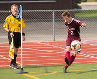 Lockport High School Soccer Player. Kicks a corner kick while the referee looks on Stock Image