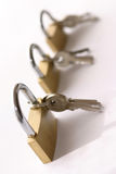Locks. Three locks in a row with thei keys on side Royalty Free Stock Image