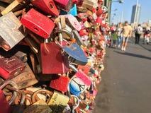 Locks as a symbol of love fastened to a bridge. Colorful locks as a symbol of love fastened to a bridge, people walking down the sidewalk in background Stock Image
