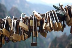 Locks of love - symbol for everlasting friendship. Padlocks lined up in promise eternal love in front of the mountain Huangshan, The keys are thrown into the stock images