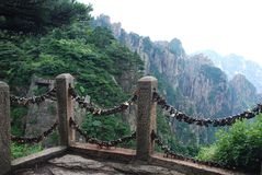 Locks of love - symbol for everlasting friendship. Padlocks lined up in promise eternal love in front of the mountain Huangshan, The keys are thrown into the stock photos