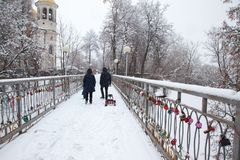 Locks with red hearts on the railing of the bridge.The backs of a family with a child. Bridge of lovers in a city park in the city of Zvenigorod in winter. The stock images