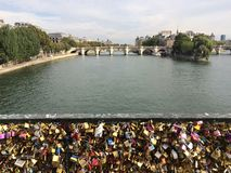 Lovers Locks on a bridge over river Seine, Paris. Romantics and lovers traditionally place locks on a bridge over river Seine in Paris, France. River Seine is Stock Image
