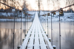 Locks on a rope bridge over frozen water royalty free stock image