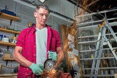 Locksmith режет металл со шлифовальным станком, механика сила увидела отрезки стоковая фотография