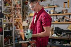 Locksmith режет металл со шлифовальным станком, механика сила увидела отрезки стоковые фото