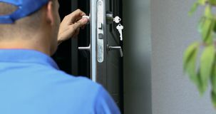 Locksmith in blue uniform installing new house door lock stock video footage