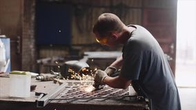 Locksmith grinds metal product after welding using angle grinder in forge shop. stock video