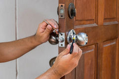 Locksmith have to fix silver knob. Wood door and locksmith maintain silver knob stock photography