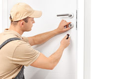 Locksmith installing a lock on a door. Studio shot of a young male locksmith installing a lock on a white door with a screwdriver isolated on white background Royalty Free Stock Photography