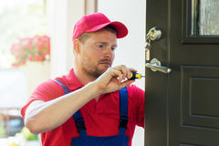 Locksmith in installing new house door lock. Locksmith in red uniform installing new house door lock stock image