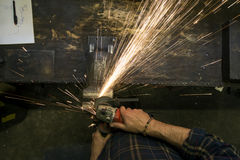 Locksmith whetting metal with flying sparks Stock Photos