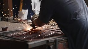 Locksmith grinds metal product after welding using angle grinder in forge shop. stock footage