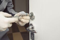 Locksmith in rag gloves changes the door locks. Selective focus, copy space royalty free stock photo