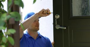 Locksmith service - man repairing house door lock stock footage