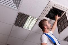 Locksmith cuts the wires in the ventilation system Royalty Free Stock Photo