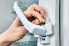 Locksmith unscrews mounting bolt of window handle, using your fi Royalty Free Stock Photography