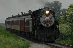 Locomotief die zich onderaan Treinsporen bewegen Stock Foto's