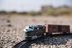 locomotief en stuk speelgoed treinwagen op het gebied wordt verlaten dat stock foto
