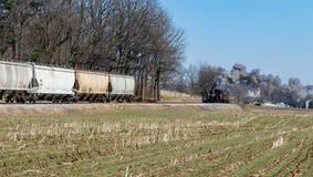 Locomotiva de vapor e para transportar carros do funil no campo Amish fotografia de stock