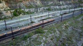 A locomotiva diesel está empurrando o descarga-carro enchido com a pedra da entulho no fundo de uma pedreira para a mineração da  filme