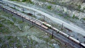 A locomotiva diesel está empurrando o descarga-carro enchido com a pedra da entulho no fundo de uma pedreira para a mineração da  video estoque