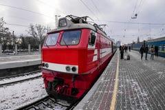 Locomotiva rossa sul binario della stazione ferroviaria nell'inverno Fotografie Stock Libere da Diritti