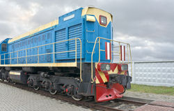 Locomotive. Of blue color is on a background of the cloudy sky Royalty Free Stock Image