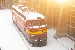 Locomotive covered with snow at the station in winter. Stock Photo