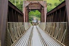 Locomotive crossing iron bridge Stock Photo