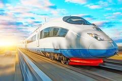 Locomotive de passager de train à grande vitesse dans le mouvement à la gare ferroviaire au coucher du soleil avec un beau ciel p Photos stock