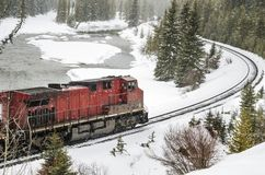 Locomotive diesel rouge sur des voies fonctionnant par une rivière pendant une tempête de neige photographie stock libre de droits