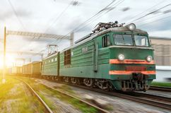 Locomotive electric with a freight train at high speed rides by rail. royalty free stock photography