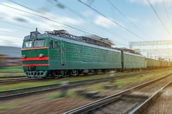 Locomotive electric with a freight train at high speed rides by rail. stock image