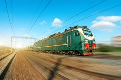 Locomotive electric with a freight train at high speed rides by rail road. Royalty Free Stock Photos