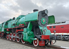Locomotive. Green of color with red wheels is on a background of the cloudy sky Stock Images