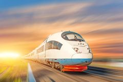 Locomotive high speed train runs on rail track, sunset sky.  stock image