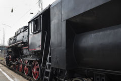 The locomotive of the last century standing under steam Stock Photography